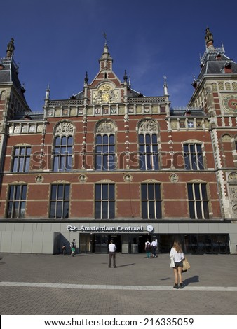 AMSTERDAM - AUGUST 27 : View of The Amsterdam central station on the 27 August 2013 in Holland, Europe. A famous tourist attraction and public transport and transportation. - stock photo