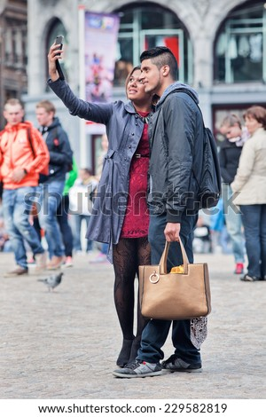 AMSTERDAM-AUGUST 26, 2014. Well dressed couple takes selfie on Dam Square. The city is a source of inspiration for fashionable people. there are many ways to soak up Amsterdam's fashionable vibe.