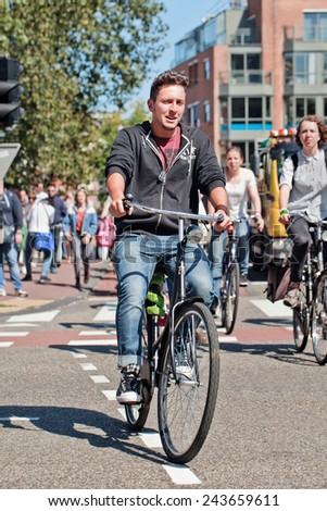AMSTERDAM-AUGUST 27, 2014. Young man enjoy riding his bike. In a city with 800,000 people, there are 880,000 bicycles, the municipal government estimates, which is four times the number of its cars. - stock photo