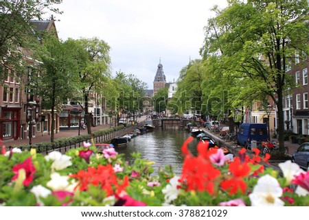 Amsterdam -Avgust 17 2015 -  Amsterdam streets and water canal with flowers. - stock photo