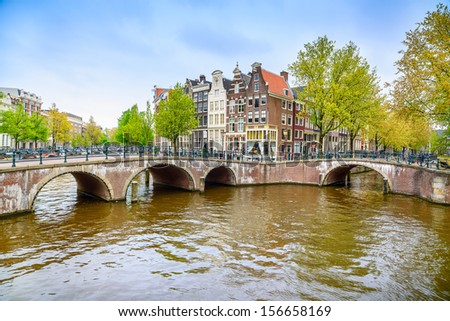 Amsterdam. Bridge and water canal on sunset. Holland or Netherlands. Europe. - stock photo