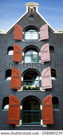 Amsterdam building, front facade of an old converted warehouse with red shutters.