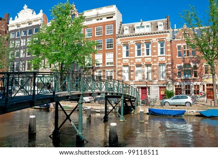Amsterdam canal and typical houses with clear summer sky - stock photo