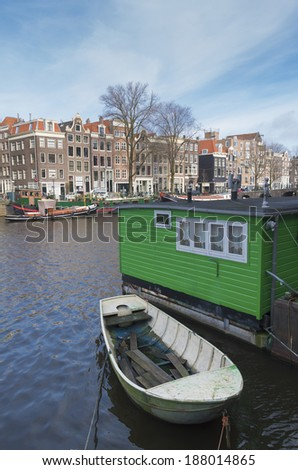 amsterdam canal with houseboat and historical houses. Most of them are very small, because in earlier ages the tax was levied on the basis of the width of the facade. - stock photo