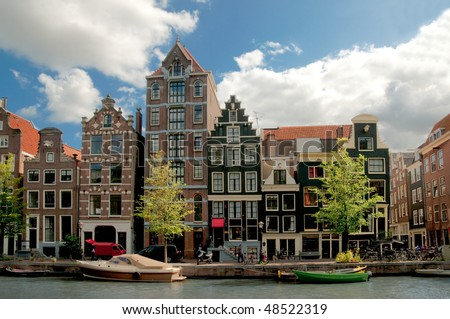 Amsterdam canals and typical houses with clear spring sky - stock photo