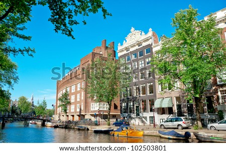 Amsterdam canals and typical houses with clear summer sky - stock photo