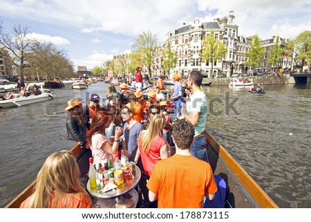 AMSTERDAM, HOLLAND - APRIL 30, 2013: Amsterdam canals full of boats and people in orange during the celebration of queensday  - stock photo