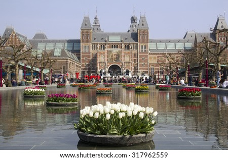 Amsterdam, Holland - April 10, 2015: Flowers in the pond in front of the Rijksuseum with billboard of Rembrandt in Amsterdam, Holland on Apil 10, 2015