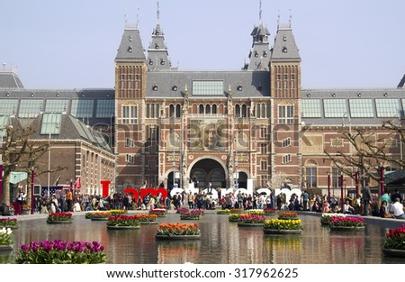 Amsterdam, Holland - April 10, 2015: Flowers in the pond in front of the Rijksuseum with billboard of Rembrandt in Amsterdam, Holland on Apil 10, 2015 - stock photo