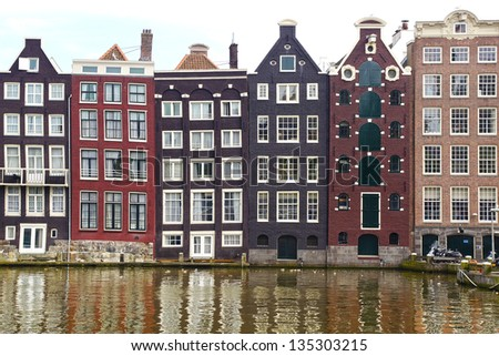 AMSTERDAM, HOLLAND - AUGUST 01:Dutch scenery with its canals and canalside houses. Typical merchant houses  buildings with a facade composed of three windows; August 01, 2012 Amsterdam, Holland - stock photo