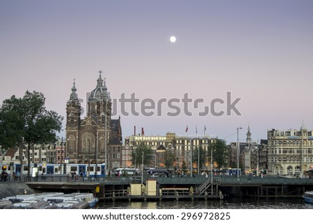 Amsterdam, Holland - June 30, 2015. Busy city centre of Amsterdam during sunset.  Amsterdam is a popular destination for tourists from all over the world.