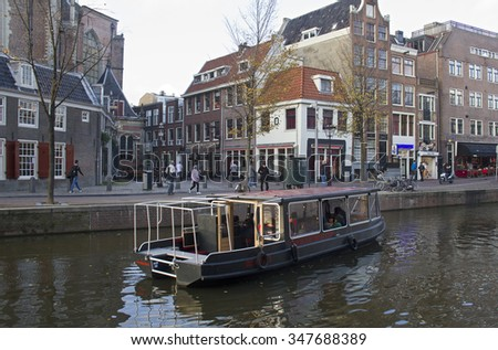 Amsterdam, Holland - November 12, 2015: Canal boat with tourists sail past prostitutes in a canal in the red light district of Amsterdam on November 12, 2015 in Amsterdam, Holland. - stock photo
