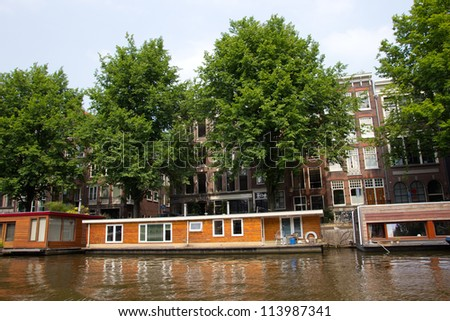 AMSTERDAM-JUL 27, 2012. Living boat on Jul 27, 2012 in Amsterdam. There are around 2,500 houseboats along 165 canals where locals live. The canal belt was added to world heritage list in July 2010 - stock photo