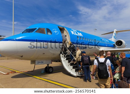 AMSTERDAM - 19 JULY, 2014: Travellers to Toulouse in France are boarding an Air France KLM Cityhopper Fokker F70 at Schiphol Airport in the Netherlands. - stock photo