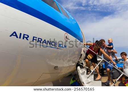 AMSTERDAM - 19 JULY, 2014: Unidentified family travelling to Toulouse in France are boarding an Air France KLM Cityhopper Fokker F70 at Schiphol Airport in the Netherlands. - stock photo