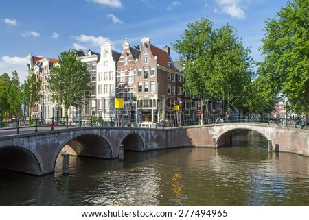 AMSTERDAM - JUN 26: Amsterdam has so many picturesque bridges adding to its lovely cityscape. Overall, Amsterdam has more than 1,200 bridges. On June 26, 2014  in Amsterdam, Netherlands - stock photo