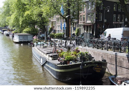 AMSTERDAM - JUNE 10: Living boat on June 10, 2011 in Amsterdam. There are around 2,500 houseboats along 165 canals where locals live. The canal belt was added to world heritage list in July 2010 - stock photo