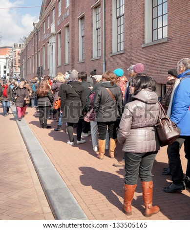 AMSTERDAM - MAR 31: Unidentified city natives and tourists stand in a long line to visit van Gogh exhibition, temporarily hosted by the Hermitage museum, March 31, 2013, in Amsterdam, The Netherlands - stock photo
