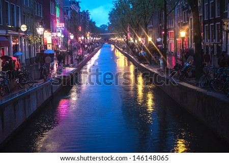 AMSTERDAM - MAY 11: Red Light District on May 11, 2013 in Amsterdam, Netherlands. There are over 500 windows in the city and about 1000 working girls. - stock photo