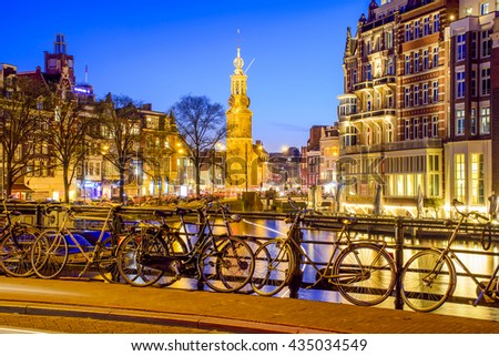 AMSTERDAM, NETHERLANDS - APRIL 9: Bicycles on the bridge over the canal at night on April, 9, 2016. Bike is one of the symbol of urban life in Amsterdam. - stock photo