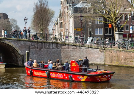 Amsterdam, Netherlands - April 2, 2016: Traditional old buildings, canal and boat in Amsterdam, Netherlands