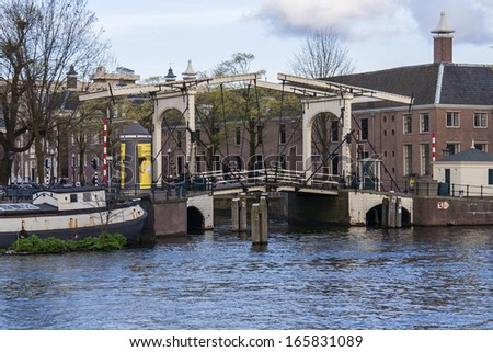 Amsterdam, Netherlands- April 13, 2012:Typical view of the canal embankment and its reflection in water in the cloudy spring morning