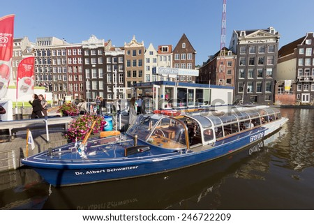 AMSTERDAM, NETHERLANDS - AUG 27 : Canal boat in front of typical Amsterdam canal houses on Aug 27, 2014. Amsterdam is the worlds most watery city. It has more than one hundred kilometres of canals. - stock photo