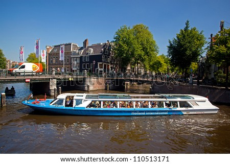 AMSTERDAM, NETHERLANDS - AUG 1: Tourist boat cruises on Prinsengracht in Amsterdam on August 1, 2012. Almost 20 percent of all canal cruise boats are now electrically powered