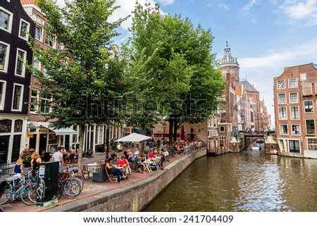 AMSTERDAM, NETHERLANDS - AUGUST 19: Canal and St. Nicolas Church in Amsterdam. Amsterdam is the capital and most populous city of the Netherlands on August 19, 2014 - stock photo