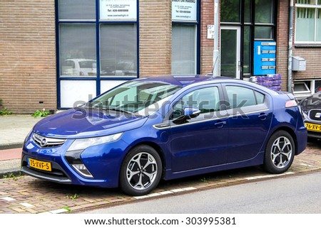 AMSTERDAM, NETHERLANDS - AUGUST 10, 2014: Electric car Opel Ampera at the city street. - stock photo