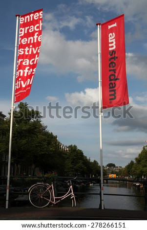 AMSTERDAM, NETHERLANDS - AUGUST 9, 2012: Old pink bicycle parked on the bridge decorated with banners with an official brand of the city in Amsterdam, Netherlands. - stock photo