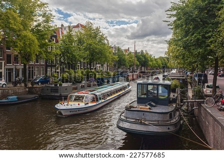 AMSTERDAM - NETHERLANDS: AUGUST 11, 2014: Tourist city sightseeing boat cruising in the canal. - stock photo