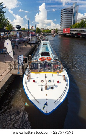 AMSTERDAM - NETHERLANDS: AUGUST 13, 2014: Tourist city sightseeing boat in canal with huge bike parking and Ibis hotel in background. - stock photo
