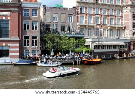 Amsterdam, Netherlands- August 10, 2013: Tourists enjoying a boat ride whilst local residents eat in the restaurant on the canal side. - stock photo