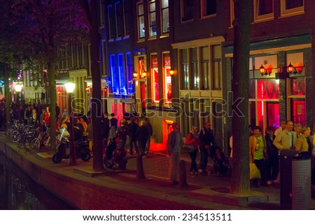 AMSTERDAM, NETHERLANDS - AUGUST 31: Tourists visit Red Light District at night on August 31, 2014 in Amsterdam, Netherlands. In this area there are prostitutes, sex shops and live sex shows - stock photo