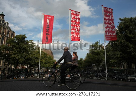 AMSTERDAM, NETHERLANDS - AUGUST 9, 2012: Two cyclists pass over the bridge decorated with banners with an official brand of the city in Amsterdam, Netherlands. - stock photo
