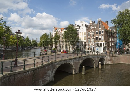 "AMSTERDAM, NETHERLANDS - AUGUST 21, 2014: View on one of the canals (Keizersgracht) with a bridge and historical houses in the famous neighborhood ""Jordaan"""