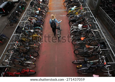 AMSTERDAM, NETHERLANDS - AUGUST 9, 2012: Woman pushes a bicycle on through the bicycle parking station next to the Central railway station in Amsterdam, Netherlands. - stock photo