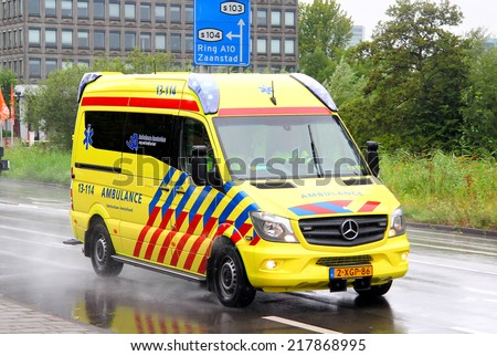 AMSTERDAM, NETHERLANDS - AUGUST 10, 2014: Yellow ambulance car Mercedes-Benz Sprinter at the city street. - stock photo