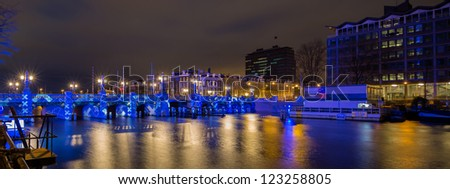 AMSTERDAM, NETHERLANDS - DEC 29: Panorama of an illuminated bridge at night during the Amsterdam Light festival in Amsterdam, the Netherlands on December 29, 2012