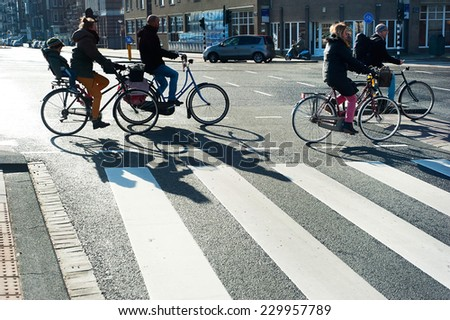 AMSTERDAM, NETHERLANDS - FEB 26, 2014: Unidentified people crossing the street by bicycle. It is one of the most cycle-friendly cities in the world. 58% of the citizens uses daily a bicycle.  - stock photo