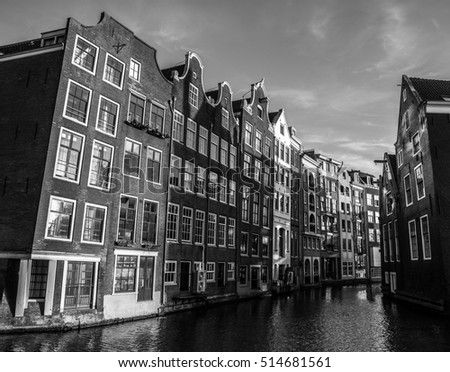 AMSTERDAM, NETHERLANDS - JANUARY 15, 2016: Black-white photo of famous buildings of Amsterdam city centre close-up at sun set time. General landscape view. Amsterdam - Netherlands.