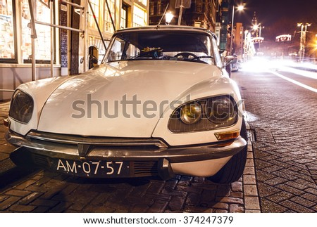 AMSTERDAM, NETHERLANDS - JANUARY 5, 2016: Vintage white car parked in center of Amsterdam at night time. January 5, 2016 in Amsterdam - Netherland. - stock photo