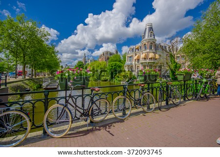Amsterdam, Netherlands - July 10, 2015: Beautiful building facade sitting waterfront, bicycles parked on bridge in front - stock photo