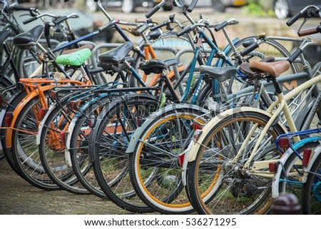 AMSTERDAM, NETHERLANDS - JULY 8, 2015: Bicycles parked in the street, of various brands and colors.