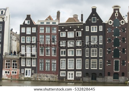 AMSTERDAM, NETHERLANDS - JULY 8, 2015: Facades of peculiar crooked buildings on the margins of the channels that run through the city.