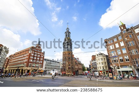 AMSTERDAM, NETHERLANDS - JULY 16: Munttoren tower with unidentified people on July 16, 2014 in Amsterdam. The tower stands on the busy Muntplein square, built 1480, rebuilt after a fire 1620  - stock photo