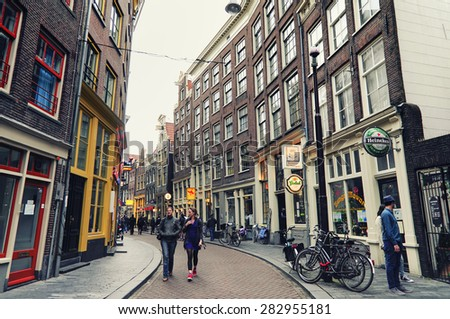 AMSTERDAM, NETHERLANDS, JULY 14, 2012: People walking at one of the streets in the old town of Amsterdam which has many coffee shops,bars and cafe's. - stock photo