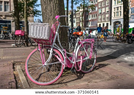 AMSTERDAM, NETHERLANDS - JULY 07, 2015: Pink bicycle leaning against a tree on the street in Amsterdam - most bicycle-friendly capital city in the world where over 60% of trips are made by bike. - stock photo