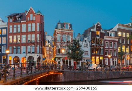 Amsterdam, Netherlands - July 30, 2014: View of the Amsterdam canals and embankments along them at night.